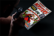 A CGC grader examines a comic book with a magnifying glass to determine its grade.