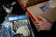 A CGC representative packages certified comic books in a cardboard box with void-filling materials.